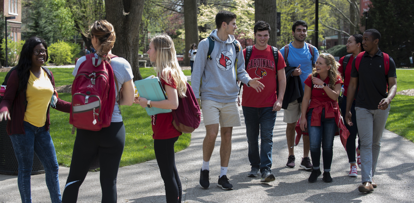 group of students on UofL's campus talking and walking