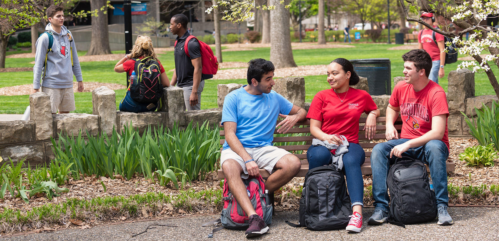 Photograph of students on UofL's campus, seated on a bench and talking.