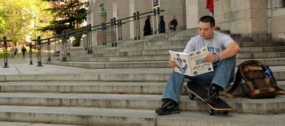 man sitting on steps outside of a building reading