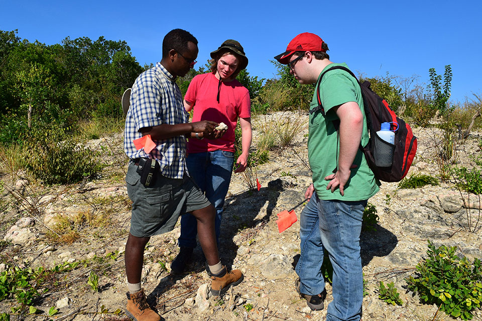 Prof. Beyin showing students a fossil in Tanzania