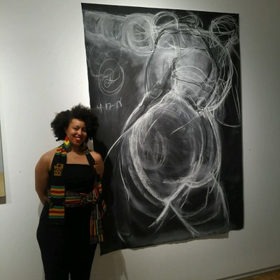 Robyn Gibson standing in front of her artwork