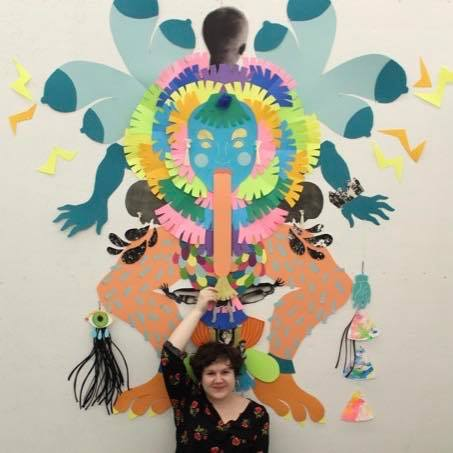 "Monica Stewart in front of paper artwork exhibited in her show titled, ""Short Cuts & Paper Tales"""