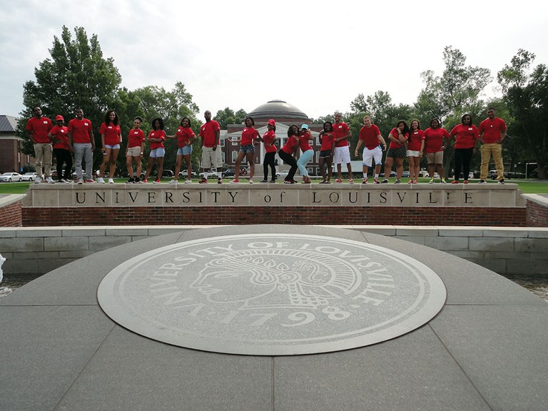 Group of students standing on the University of Louisville main entrance wall.