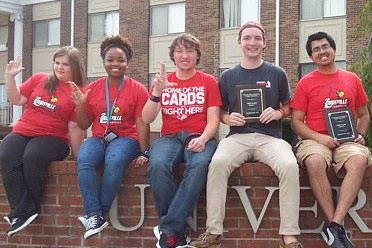 Students sitting in a row on a wall holding their Quiz Bowl awards