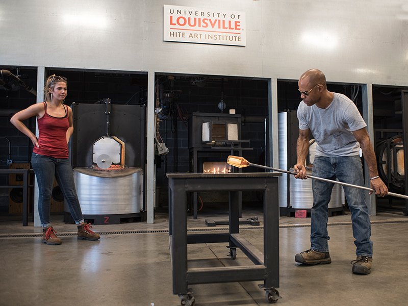 man and woman work in art studio blowing glass