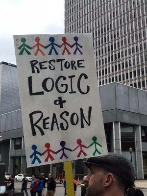 Person holding sign that says Restore logic and reason in March for Science