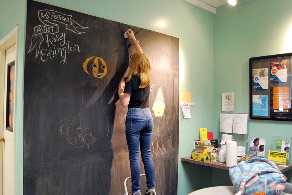 Kasey Edrington making art on the A&S Advising chalk board