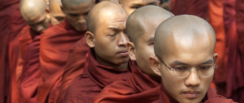 Monks in redish-orange robes in line