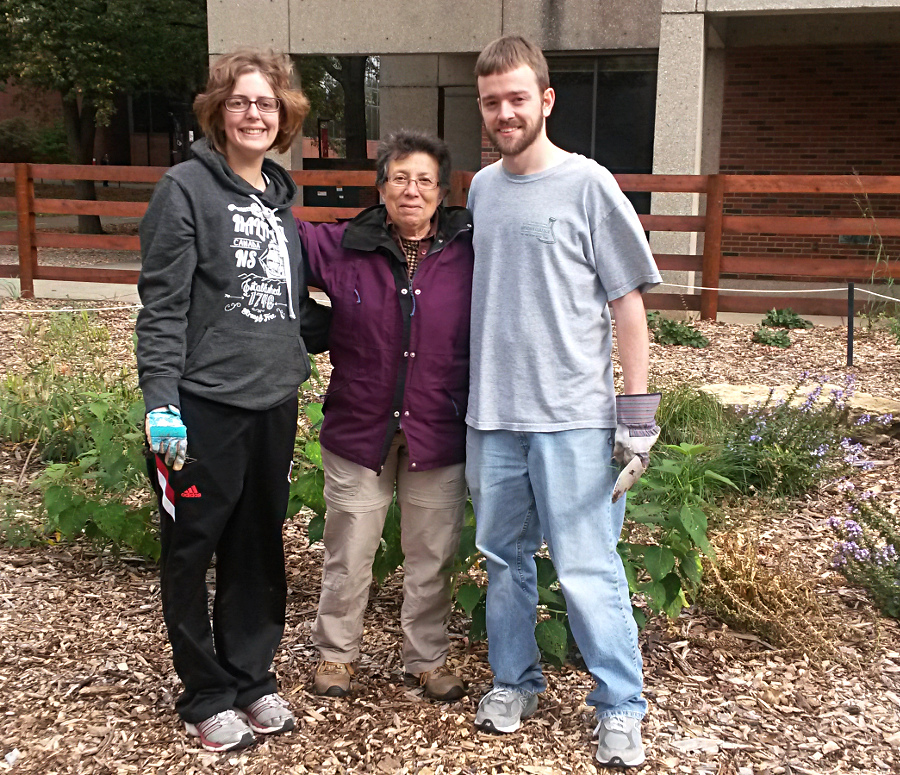 Dr. Margaret Carreiro (middle) happy to have help weeding and watering the garden fromgraduate students Lindsay Nason (left) and Matt Reid (right).