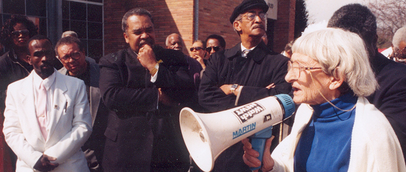Anne Braden with megaphone speaking to crowd of African Americans