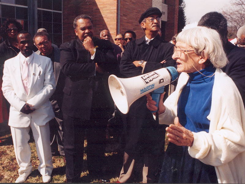Anne Braden speaking to group with megaphone
