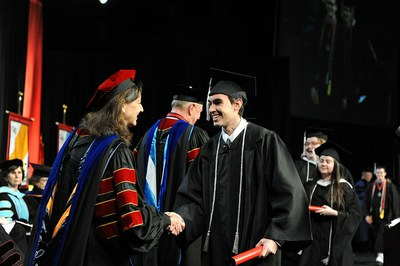 Male student shaking hands with the Provost while crossing the stage at commencement
