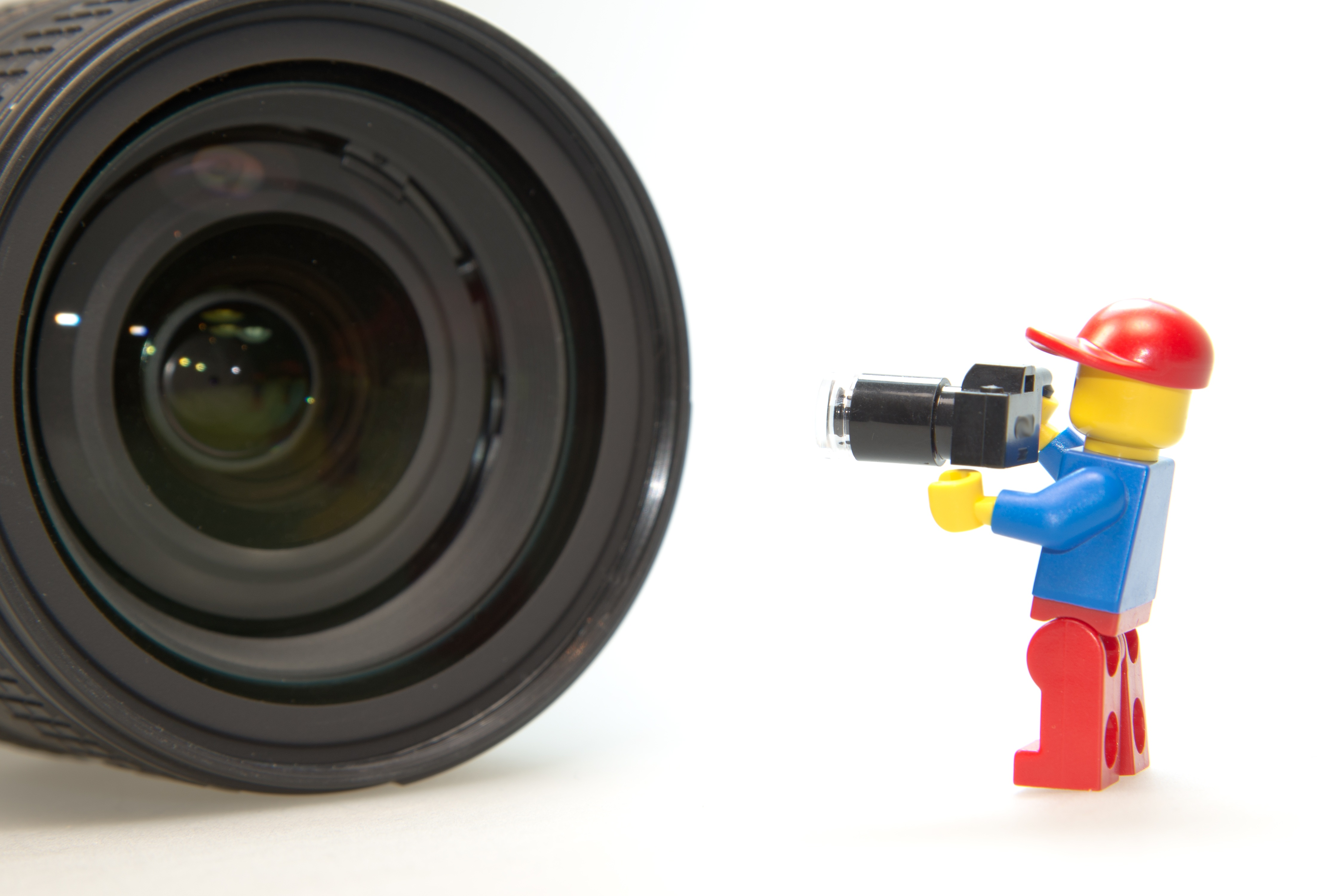 LEGO figure holding toy camera pointed at real camera lens