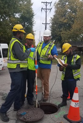 4 men inspecting a local sewer