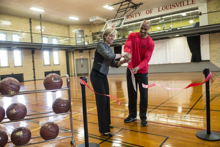 Patricia Benson and Darrell Griffith cut ribbon to newly opened basketball court at Fitness Center