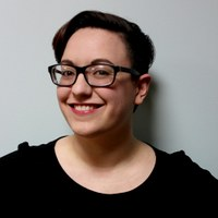 An image of a Alex O'Keefe. A woman smiling, wearing glasses against a plain wall.