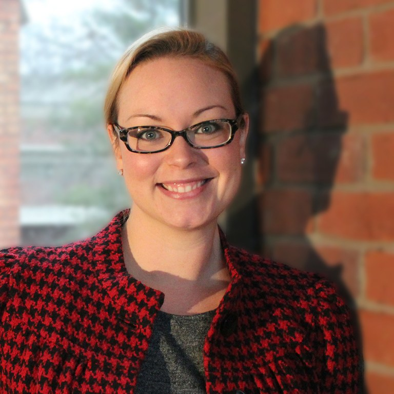 A woman wearing glasses standing in front of a brick wall.
