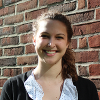 An image of advisor, Sarah Exner, standing in front of a brick wall.