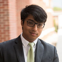 Ajit Deshpande; a scholar wearing a gray suit with a green tie and glasses standing outside in front of a brick wall.