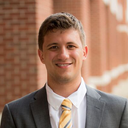 Eric Elder; a scholar wearing a gray suit with a yellow striped tie standing outside in front of a brick wall.
