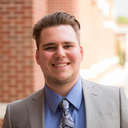 Nicholas Zalla; a scholar wearing a gray suit with a blue paisley tie standing outside in front of a brick wall.