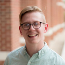 Bayne Lutz; a scholar wearing a mint button-down shirt and glasses standing outside in front of a brick wall.