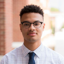 Benjamin Anderson; a scholar wearing a plaid shirt and blue tie standing outside in front of a brick wall.
