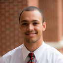 Christopher Wesley; a scholar wearing a white shirt and UofL tie standing outside in front of a brick wall.