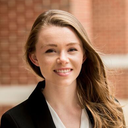 Danielle Graves; a scholar wearing a black blazer standing outside in front of a brick wall.