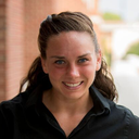Emma Ison; a scholar wearing a black dress shirt standing outside in front of a brick wall.