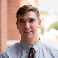 Andrew Arcieri; a scholar wearing a blue shirt and red tie standing outside in front of a brick wall.