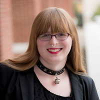 Madison Dalton; a scholar wearing a black blazer and choker necklace standing outside in front of a brick wall.