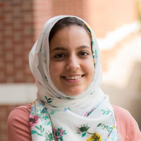 Rianne Kablan; a scholar wearing a pink shirt and white floral headscarf standing outside in front of a brick wall.