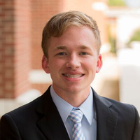 Ryan Crum; a scholar wearing a black suit and blue tie standing outside in front of a brick wall.