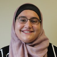 Nora Alshimary; a scholar in a black shirt and pink headscarf stands against a blank wall.
