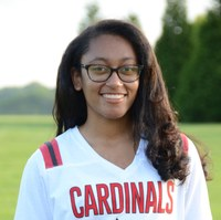 An image of a young woman of color wearing glasses and a Cardinals jersey. Her hair is long and wavy. She is standing outside in a green field.