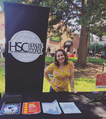An image of Allison LaRoy, a student in a yellow floral shirt, standing outside at a table. Behind the table is a black banner with an owl logo that reads