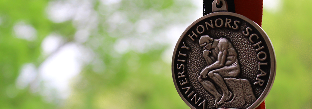 The Honors Scholar graduation medal against an outdoor background.