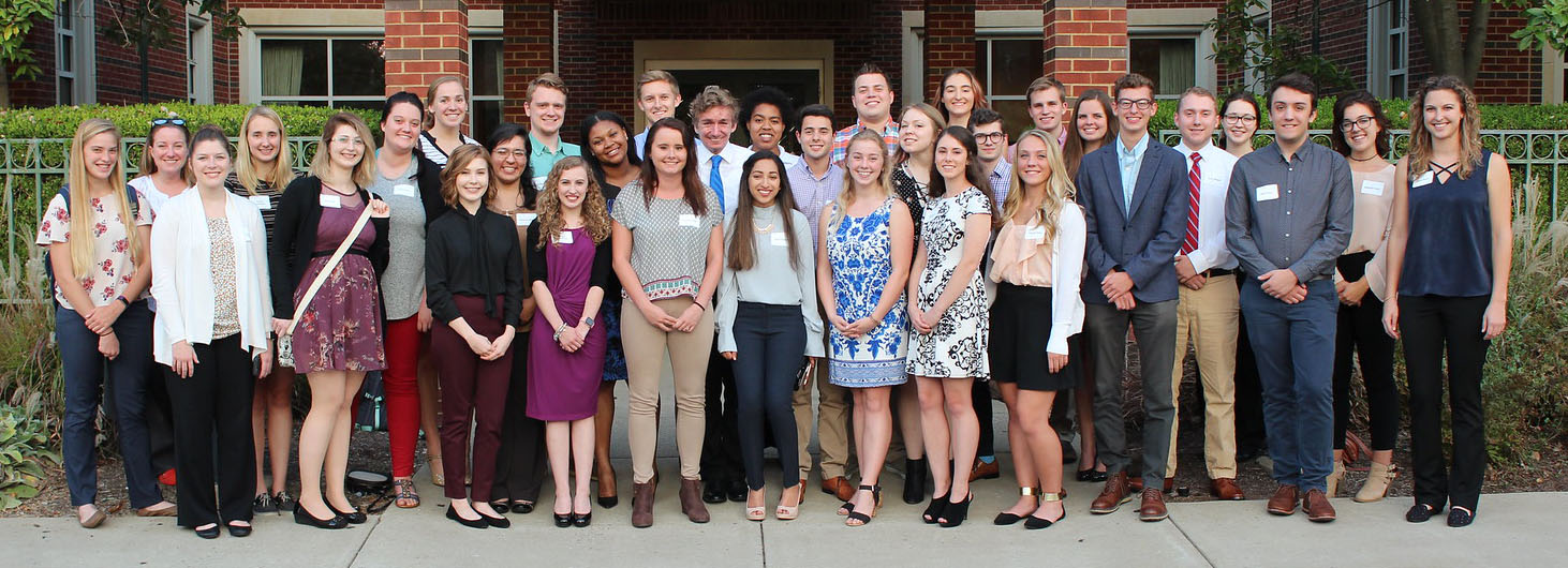 A group of students stands outside dressed in business-casual clothing.