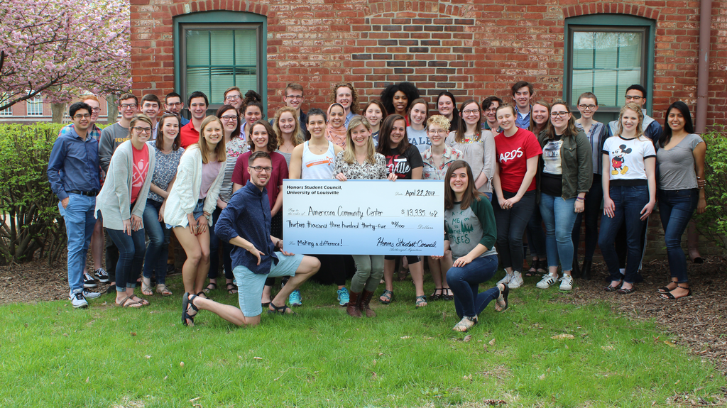 An image of a large group of students from the Honors Student Council standing outside in front of a brick building. The students closest to the camera are holding an over-sized check made out to the Americana Community Center.