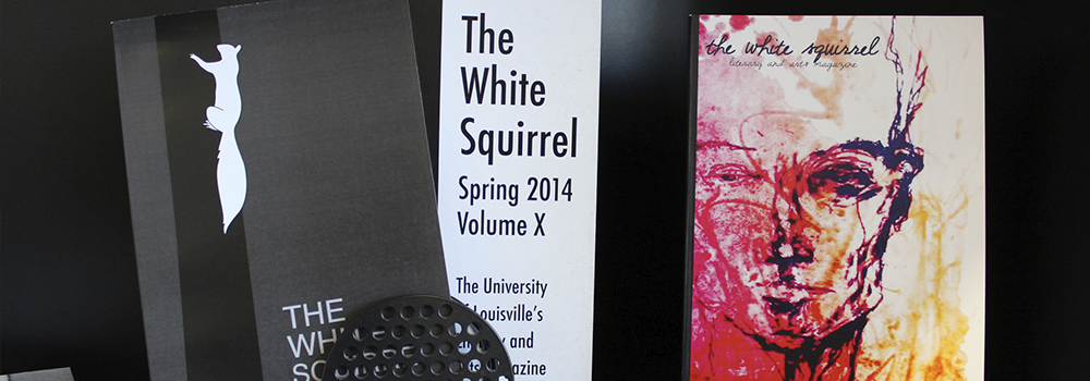 An image of three issues of The White Squirrel Literary and Arts Magazine propped up. The leftmost book cover has a squirrel on it, the middle book cover has