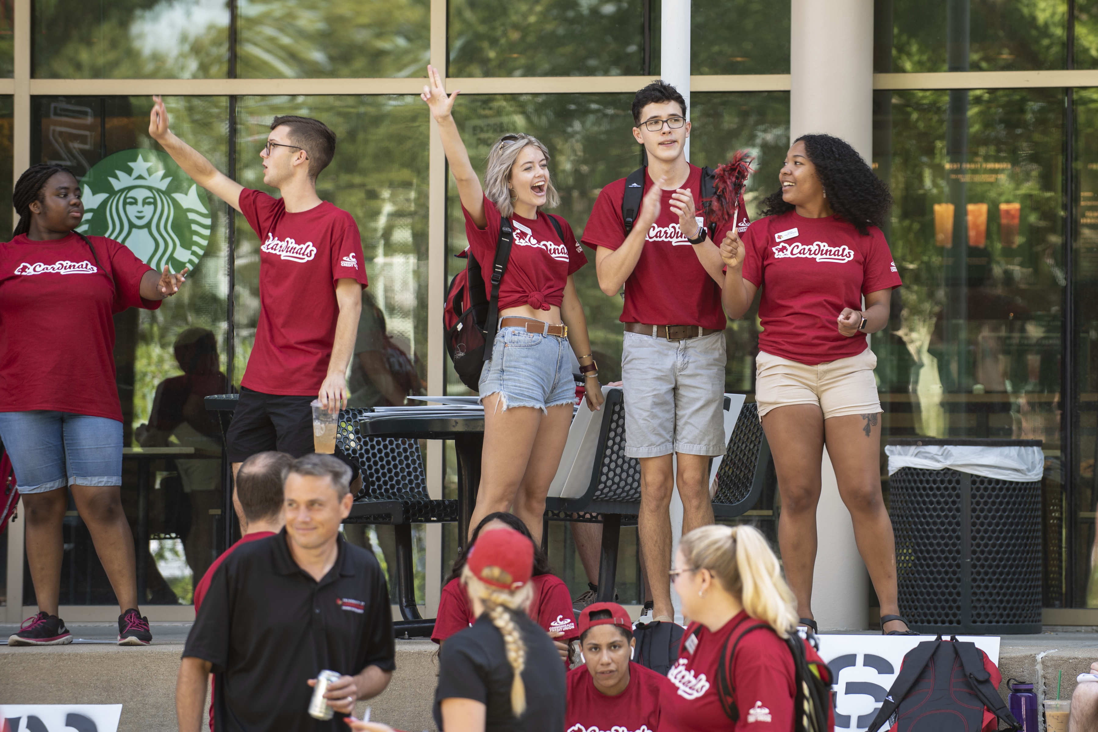 photos of students in cardinal t-shirts in front of Ekstrom library. attending alumni picnic event
