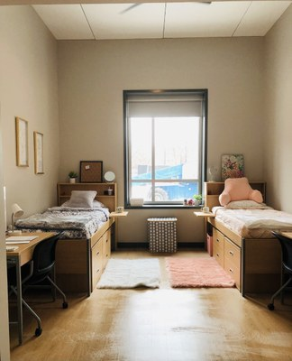 double room. Two beds on left and right with ceiling fan at top. There is a large window behind both beds.