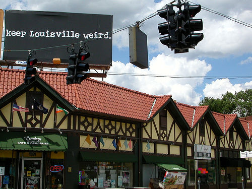 picture of a corner store with a large billboard over it reading, keep Louisville weird.