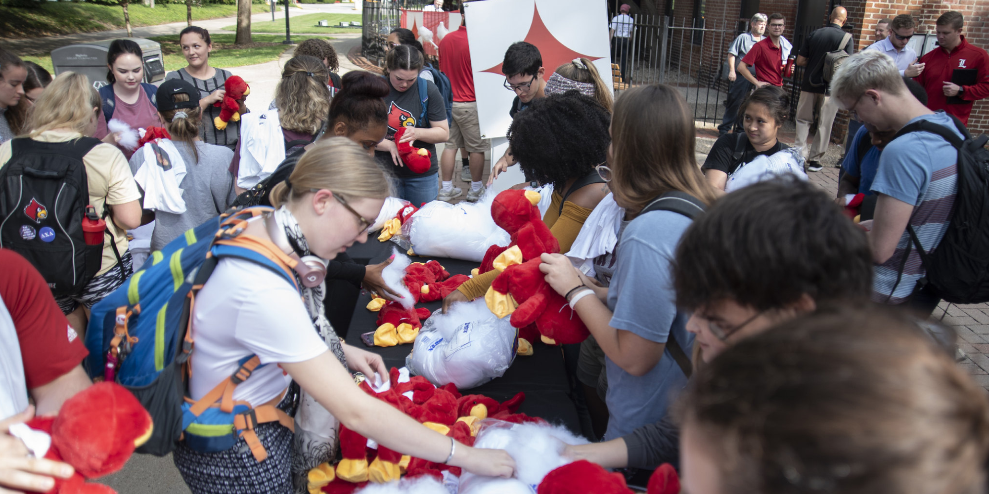 Students gathered around a table stuffing plush cardinal birds