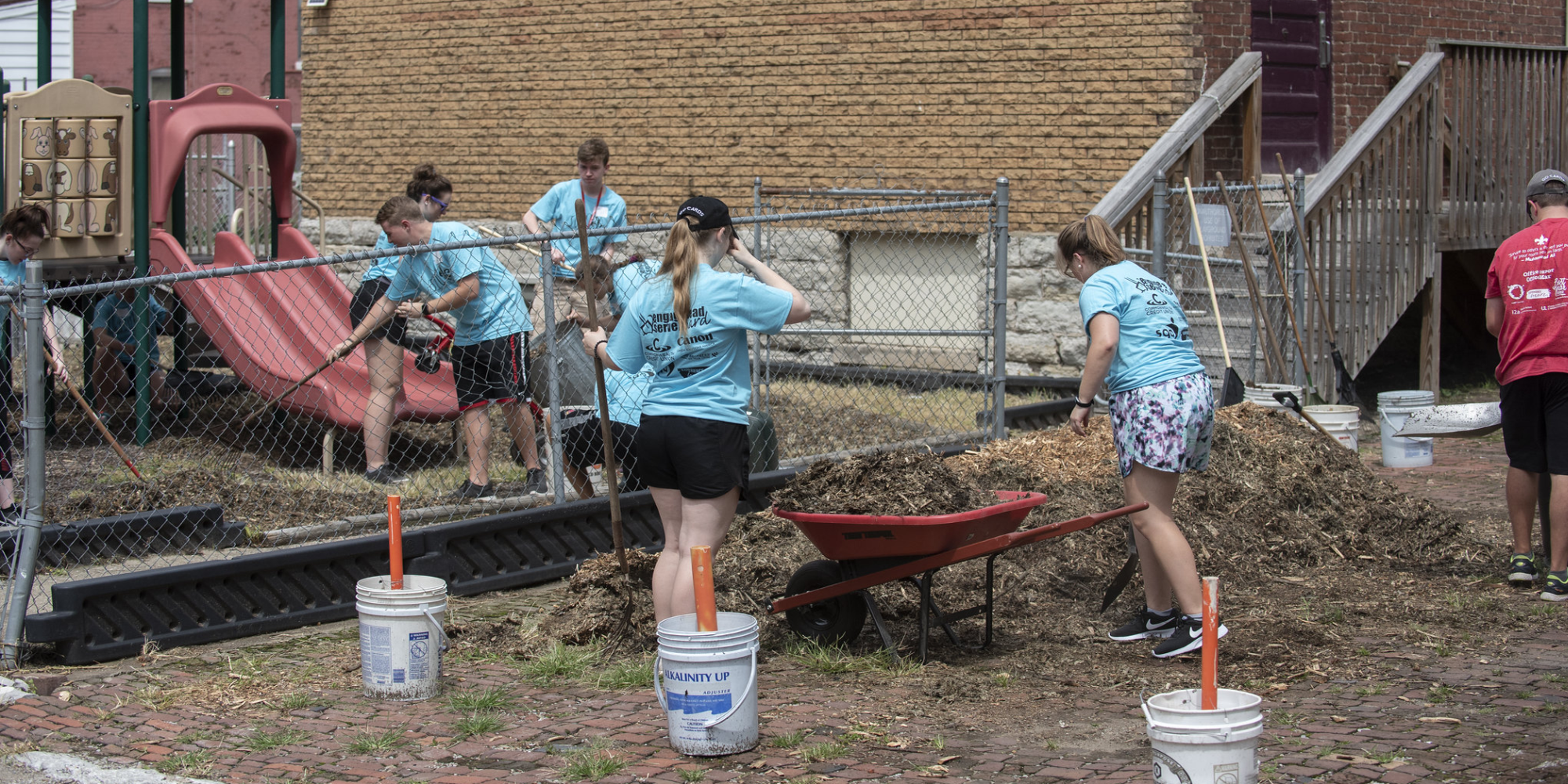 Spreading mulch onto a play area during a S.O.U.L event