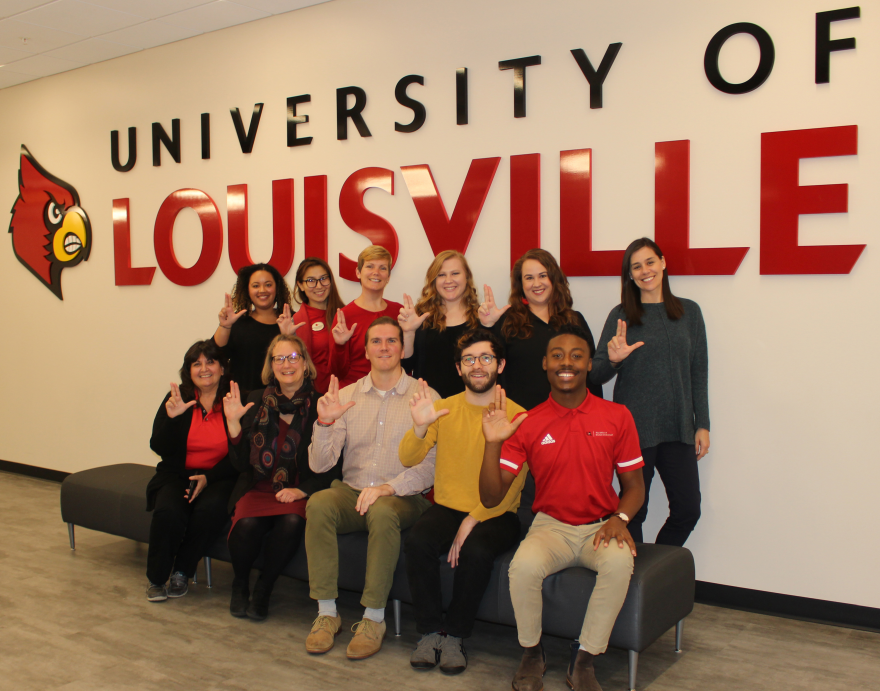group picture of the Student Involvement staff posing in front of a University of Louisville sign