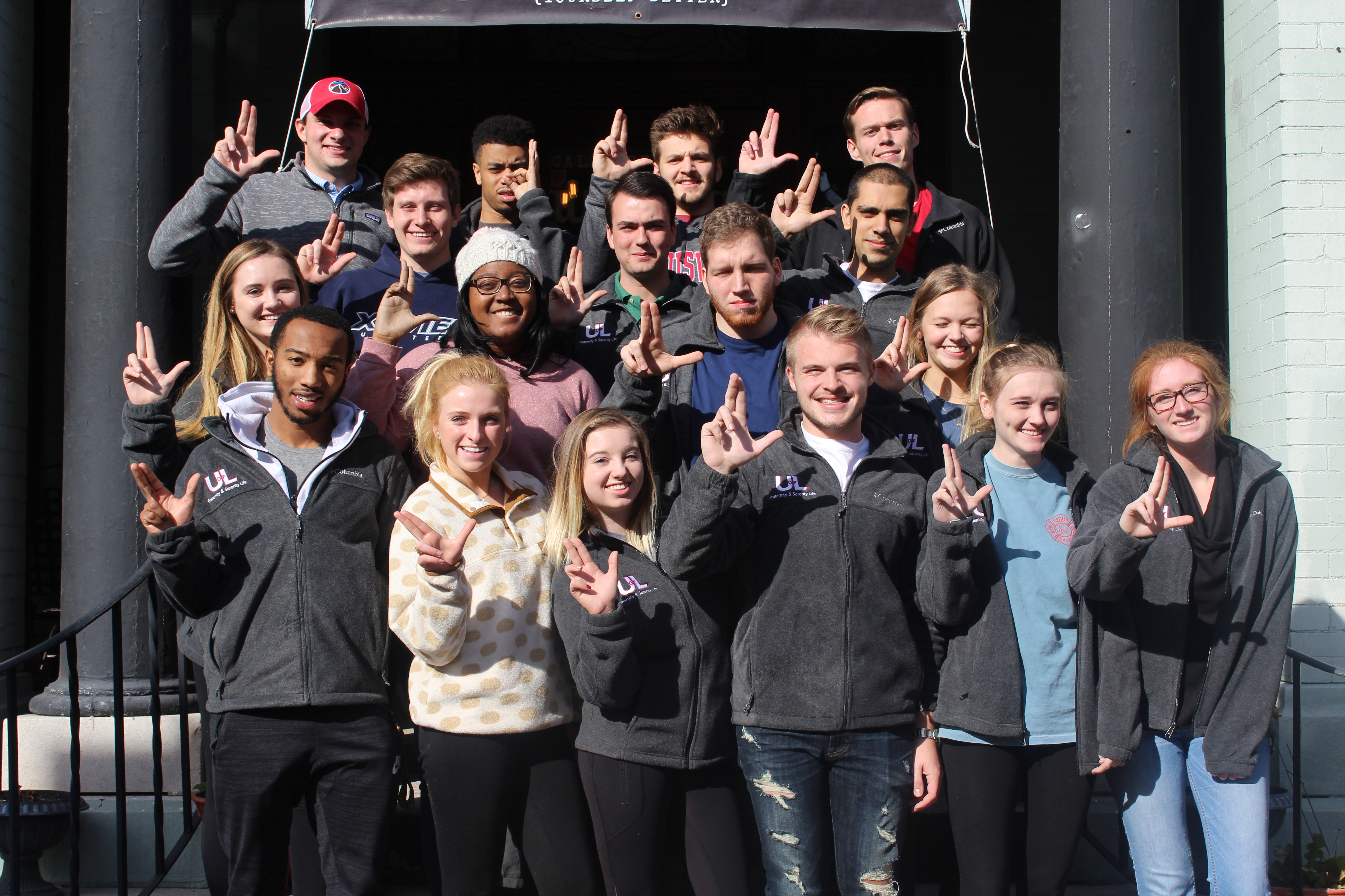 diverse group of students smiling and holding up the L sign