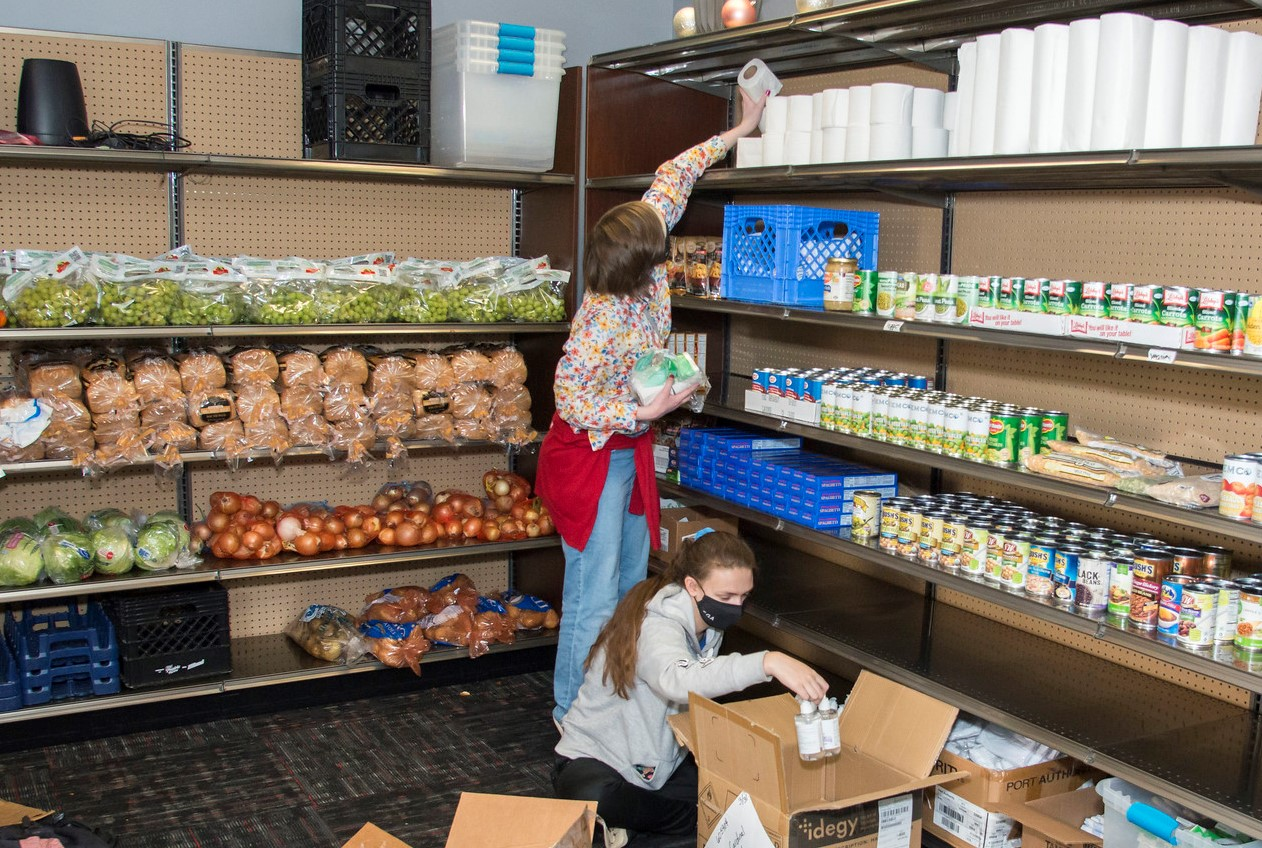 two student volunteers stocking shelves with products in the Cardinal Cupboard.