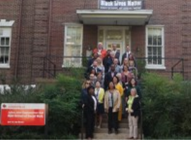 picture of Kent School faculty and staff in front of the banner